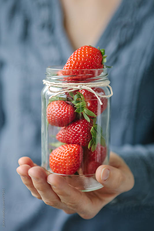 Hands Holding Strawberries in a glass jar by Zocky for Stocksy United
