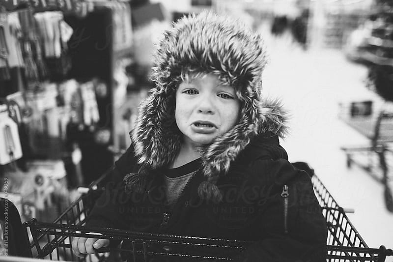 A little boy in a furry hat crying in a shopping cart. by Sarah Lalone for Stocksy United