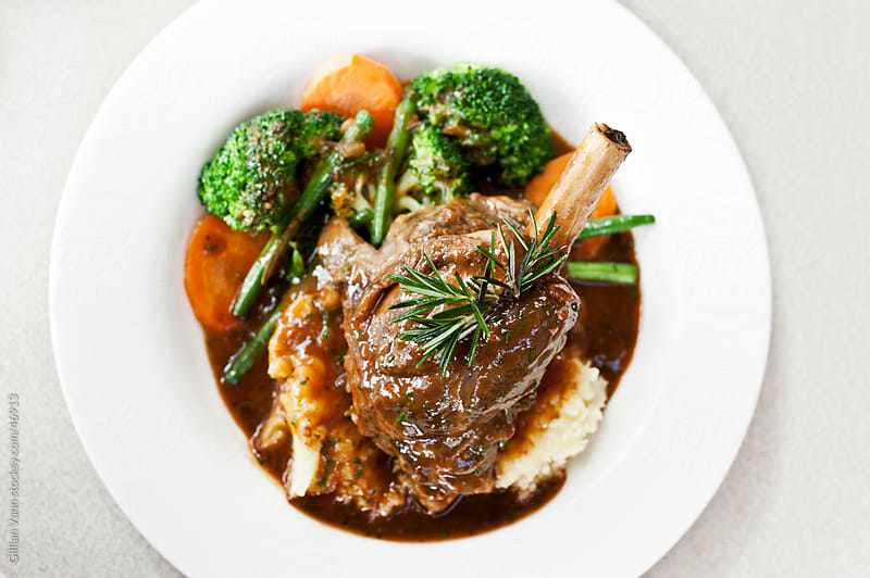 lamb shank on white plate by Gillian Vann for Stocksy United