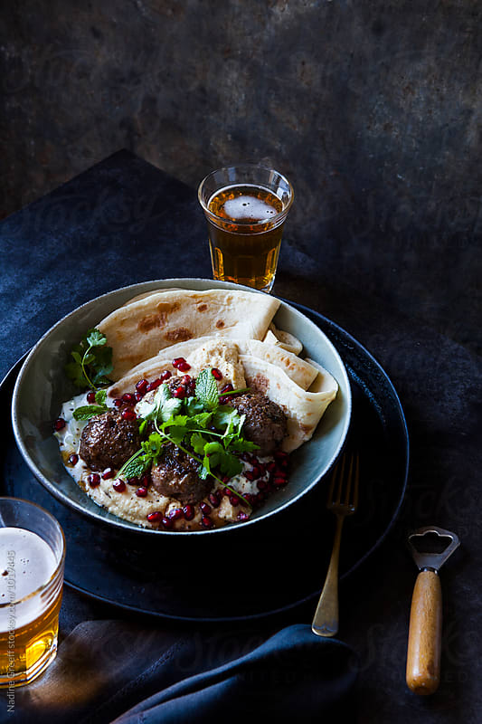 Spicy lamb meatballs with hummus, pomegranate, cucumber mint yoghurt and flat bread by Nadine Greeff for Stocksy United