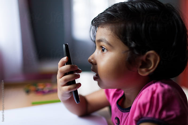 Little girl talking on mobile phone in speaker mode by Saptak Ganguly for Stocksy United