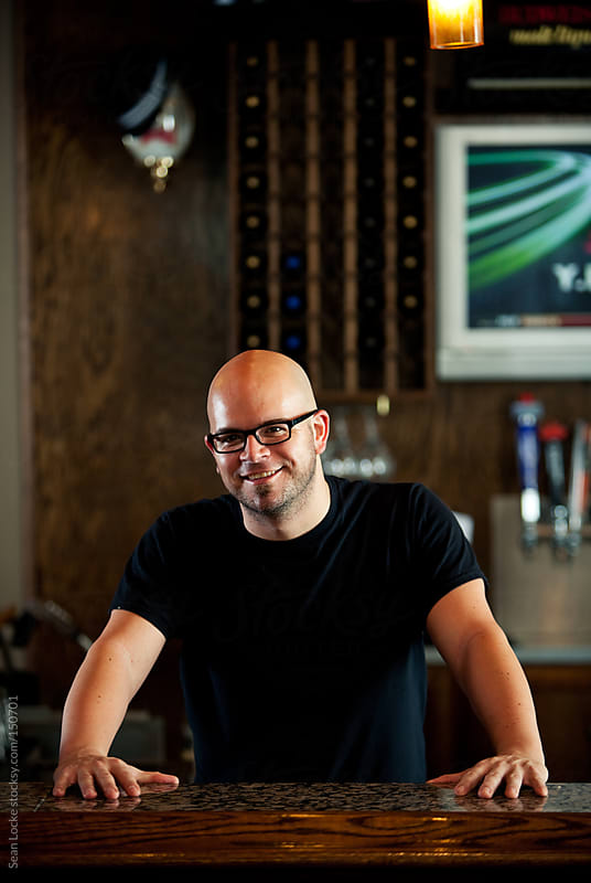 Bar: Cheerful Bartender Tends Bar by Sean Locke for Stocksy United