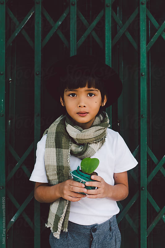 Handsome Asian boy holding a little plant pot by Nabi Tang for Stocksy United