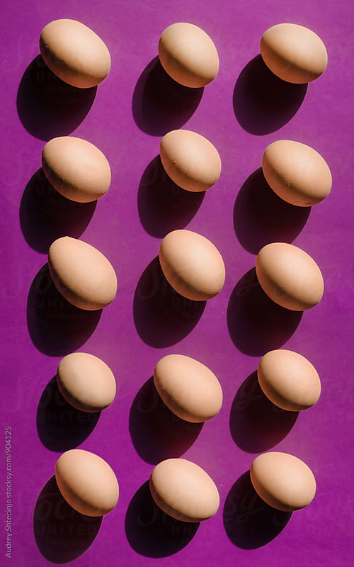Well organised bunch of eggs on purple background by Audrey Shtecinjo for Stocksy United