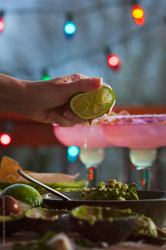 Fiesta: Squeezing A Lime For Juice Into Guacamole by Sean Locke for Stocksy United