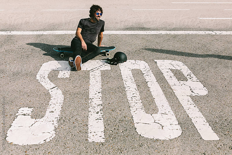 Young Man Sitting with a Longboard in front of a Stop Road Sign by VICTOR TORRES for Stocksy United