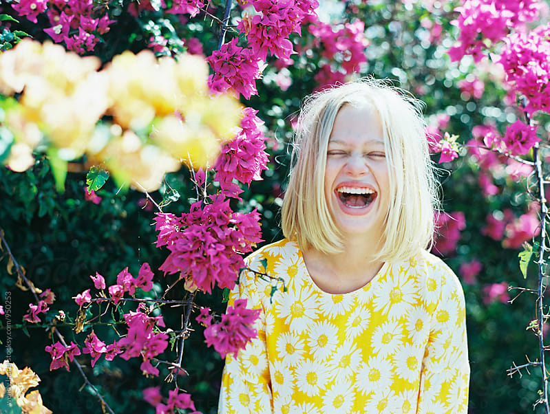 blonde girl laughing out loud in front of pink and yellow flowers by wendy laurel for Stocksy United