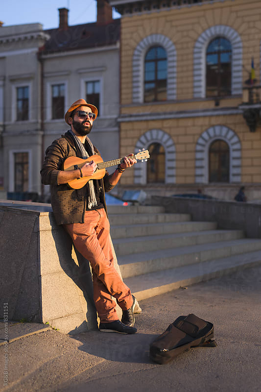 Man standing in the sunlight playing music on the street by RG&B Images for Stocksy United