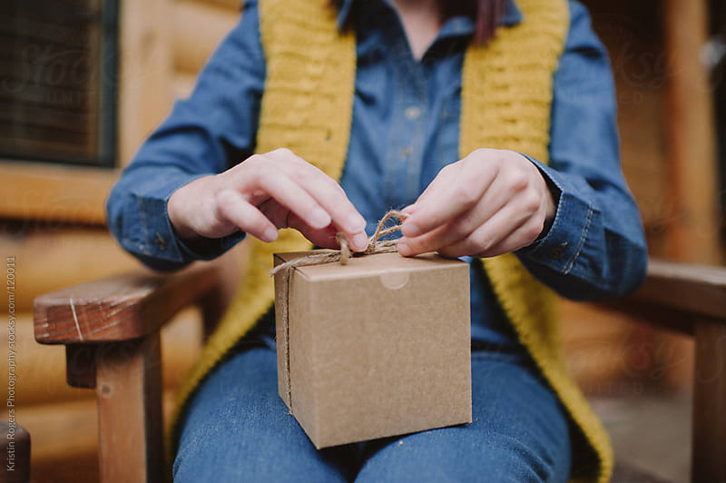 Woman wrapping gift on porch of cabin by Kristin Rogers Photography for Stocksy United