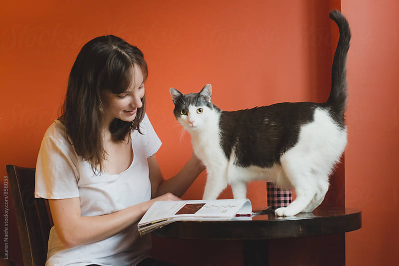 Young woman and cat at home by Lauren Naefe for Stocksy United