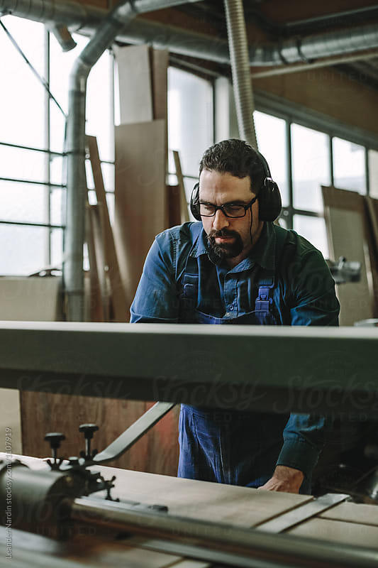 portrait of a bearded woodworker with black  protection earmuffs working on a belt sander