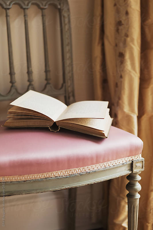 Open book laying on a chair by Ellie Baygulov for Stocksy United