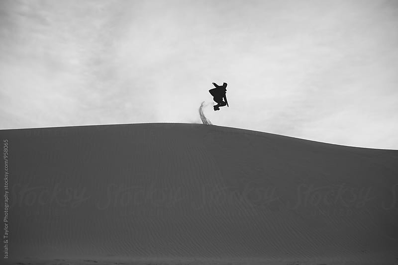 Man jumping off sand dune by Isaiah & Taylor Photography for Stocksy United