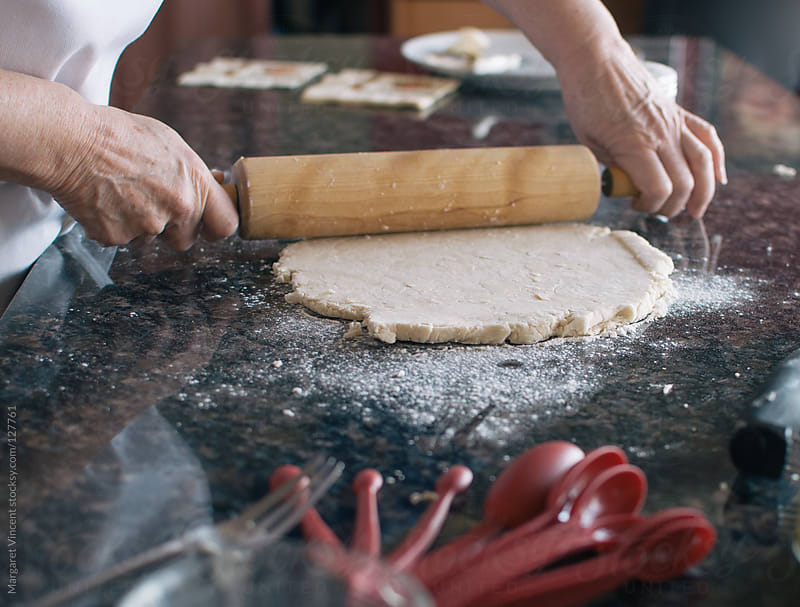 woman rolling out pie crust by Margaret Vincent for Stocksy United