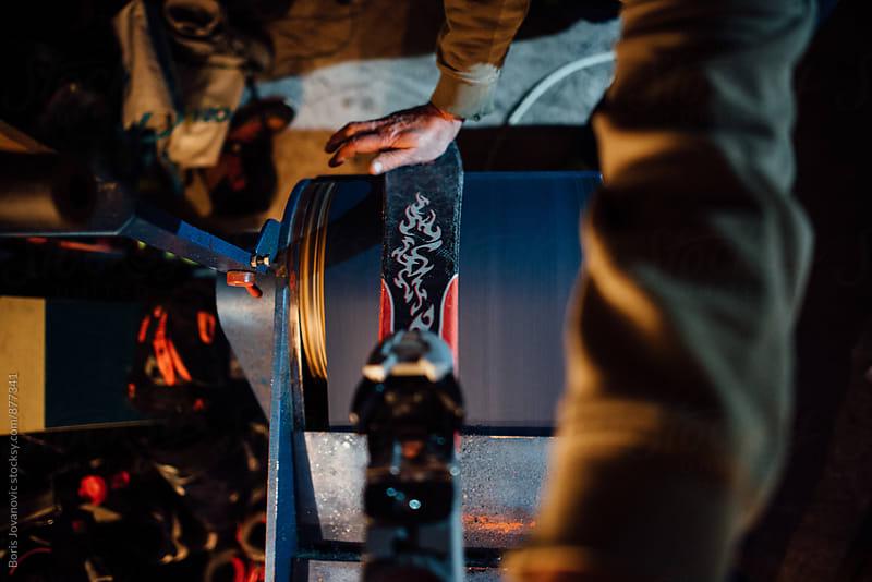 Man repairing a ski base on the emery paper machine by Boris Jovanovic for Stocksy United