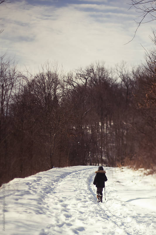 Young Boy Hiking on a Snow Covered Trail by Kevin Keller for Stocksy United