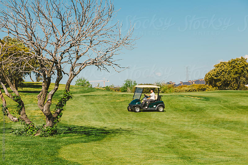 Golfer Driving a Golf Cart by VICTOR TORRES for Stocksy United