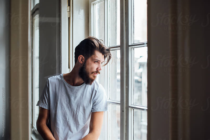 Handsome Bearded Man Looking Thought the Window by Nemanja Glumac for Stocksy United