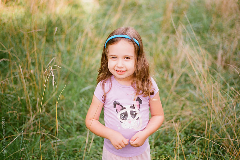 Portrait of a beautiful young girl standing in a field with tall grass by Jakob for Stocksy United
