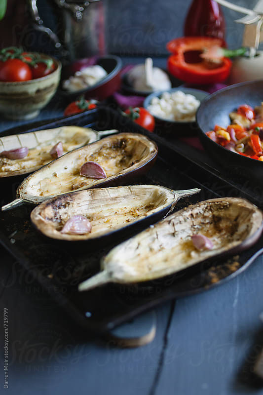 Roasted aubergine shells with garlic ready. by Darren Muir for Stocksy United
