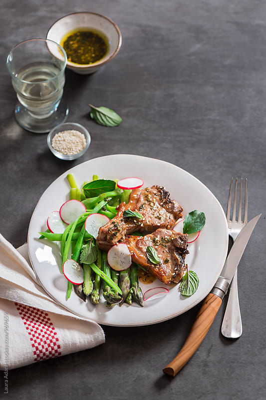 Sauteed lamb chops with asparagus and radishes salad by Laura Adani for Stocksy United