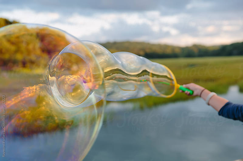 Girl Making Bubbles at Outdoor Birthday Party in Summer by Raymond Forbes LLC for Stocksy United