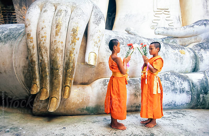 Novice monks and Phra Atchana Buddha statue, Wat Si Chum, Sukhothai, UNESCO World Heritage Site, Sukhothai Province, Thailand, Asia by Gavin Hellier for Stocksy United