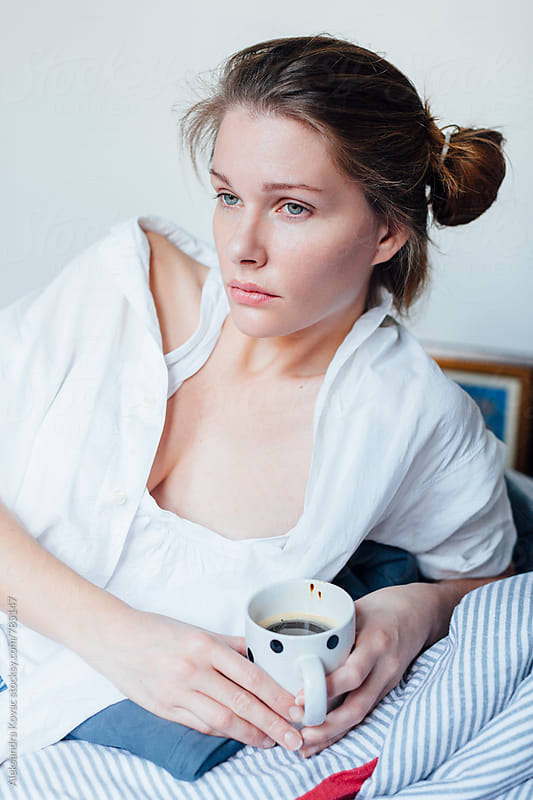 Woman drinking coffee in bed in the morning by Aleksandra Kovac for Stocksy United
