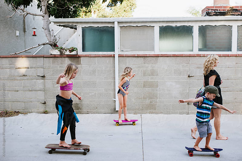 Group of kids skateboarding with mom down alley by Kristin Rogers Photography for Stocksy United