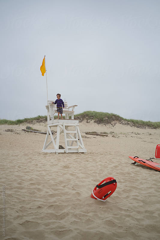 Young Boy on a life guard chair in Cape Cod. by Lucas Saugen for Stocksy United