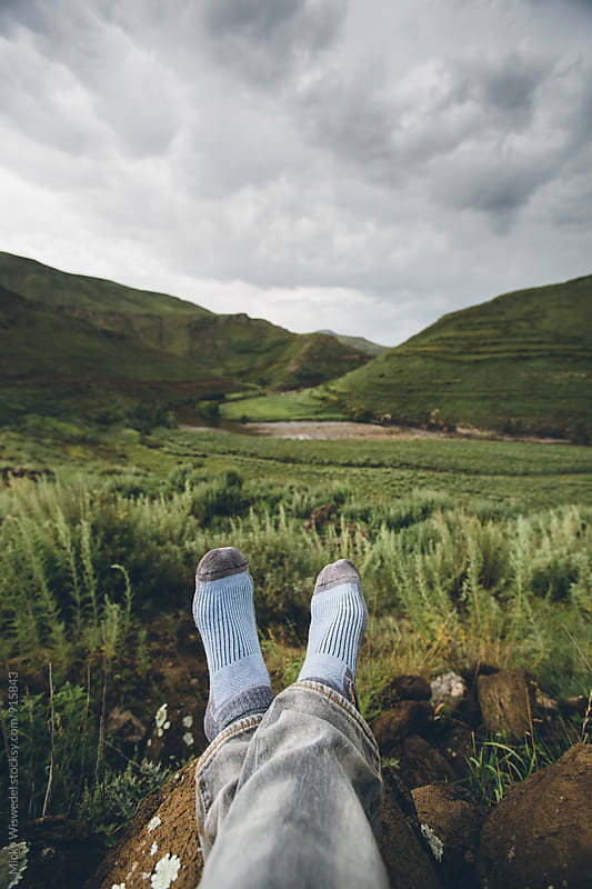 Hikers feet and socks with a mountainous valley view in the background by Micky Wiswedel for Stocksy United