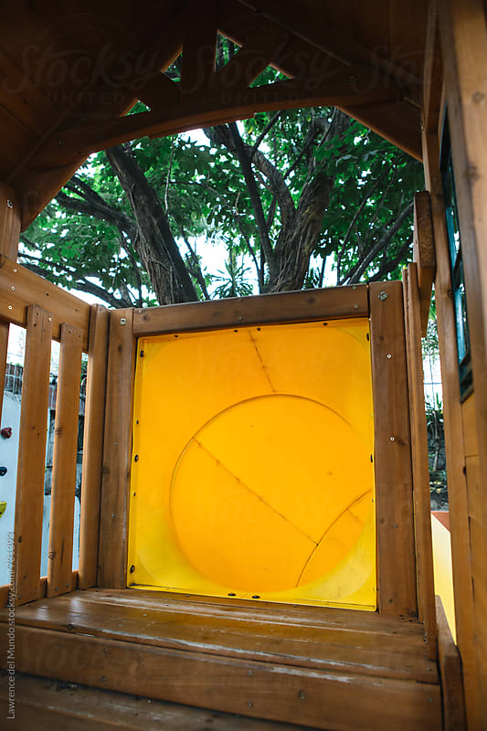 Entrance to the yellow tube slide in the playground by Lawrence del Mundo for Stocksy United