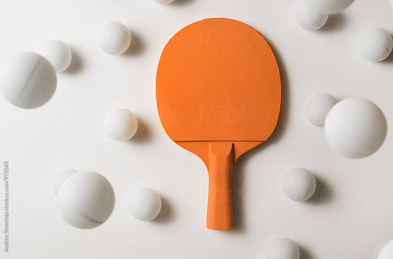 Orange pIng pong racket and white balls flying by Audrey Shtecinjo for Stocksy United