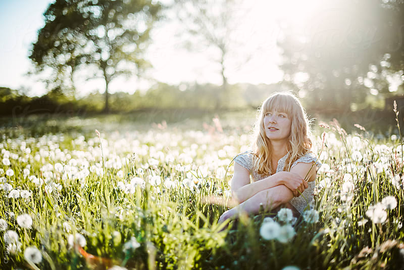 a girl sitting in a meadow with dandelions by Chris Zielecki for Stocksy United
