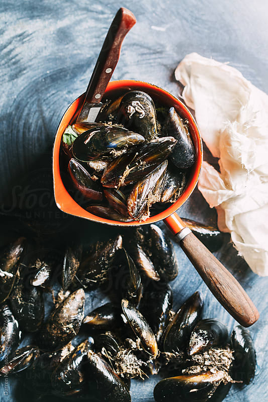 Mussels ready to be cleaned before cooking. by Darren Muir for Stocksy United