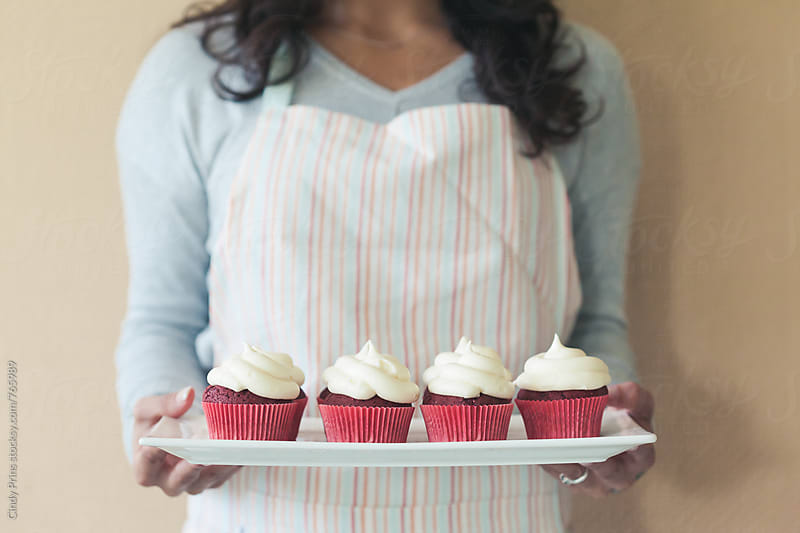 Woman holding a plate of red velvet cupcakes by Cindy Prins for Stocksy United