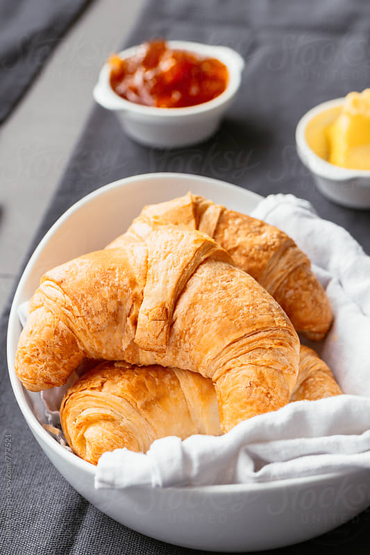 croissant for breakfast. with jam and butter by Gillian Vann for Stocksy United