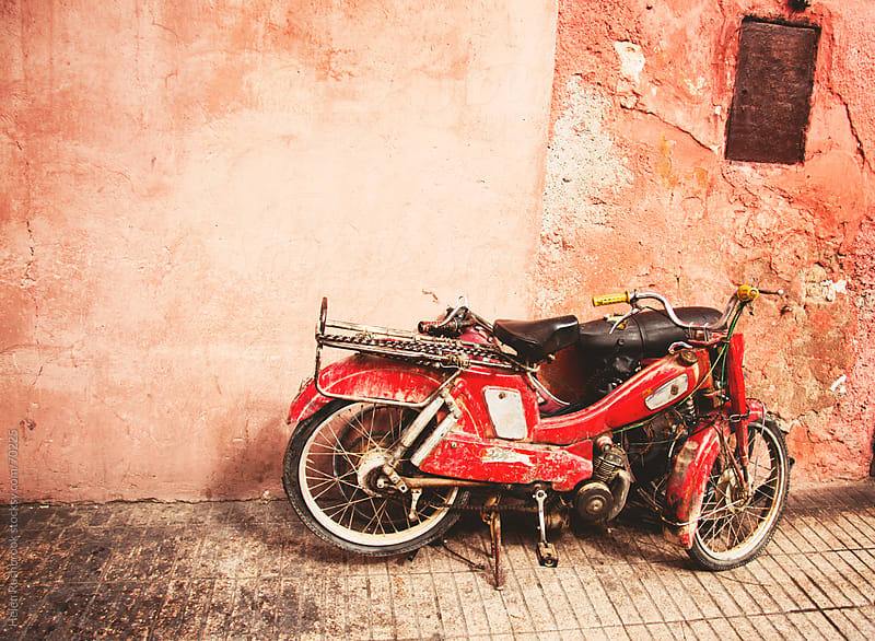 A red motorbike leaning against a brightly painted wall in Morocco. by Helen Rushbrook for Stocksy United