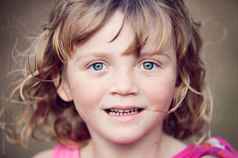 Young girl with beautiful blue eyes smiling  by anya brewley schultheiss for Stocksy United