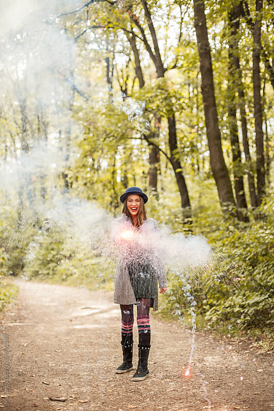 Young Woman Playing With Smoke Bomb in the Forest by Mosuno for Stocksy United