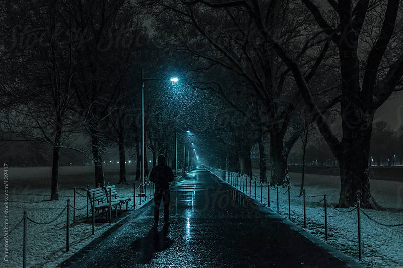Man on a snowy path at night by Cameron Whitman for Stocksy United