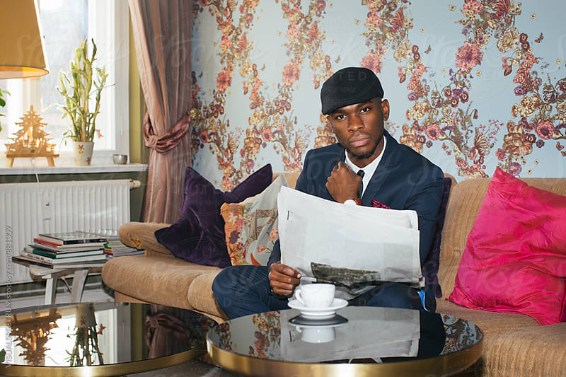 Elegant Young Black Man Reading Newspaper in Colorful Living Room by Julien L. Balmer for Stocksy United