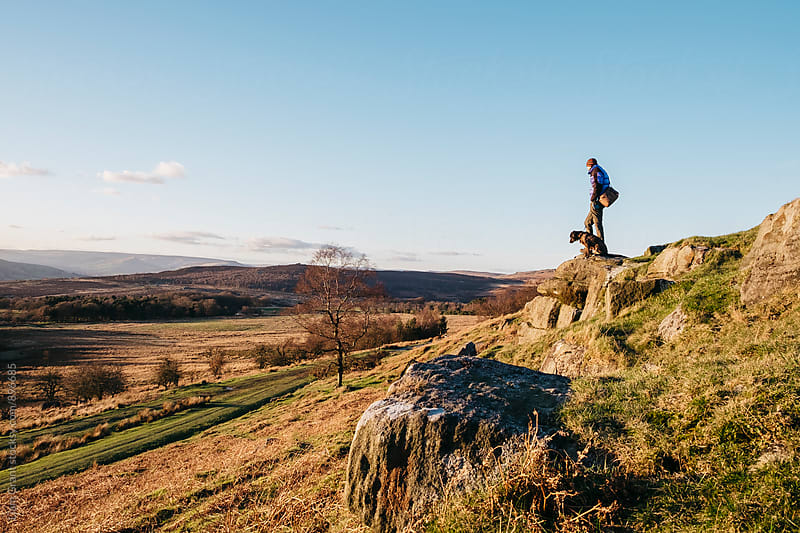 Male and his dog on a hilltop at sunset. Upper Padley, Derbyshire, UK. by Liam Grant for Stocksy United