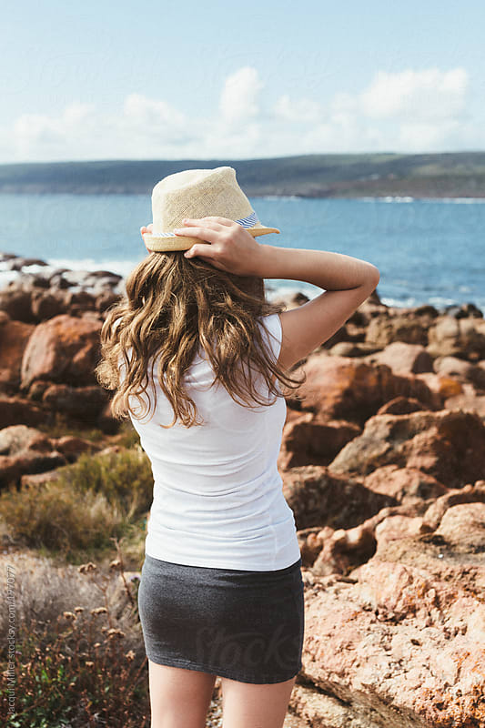 Back view of cute teenage girl holding her hat on her head while looking out at the ocean by Jacqui Miller for Stocksy United