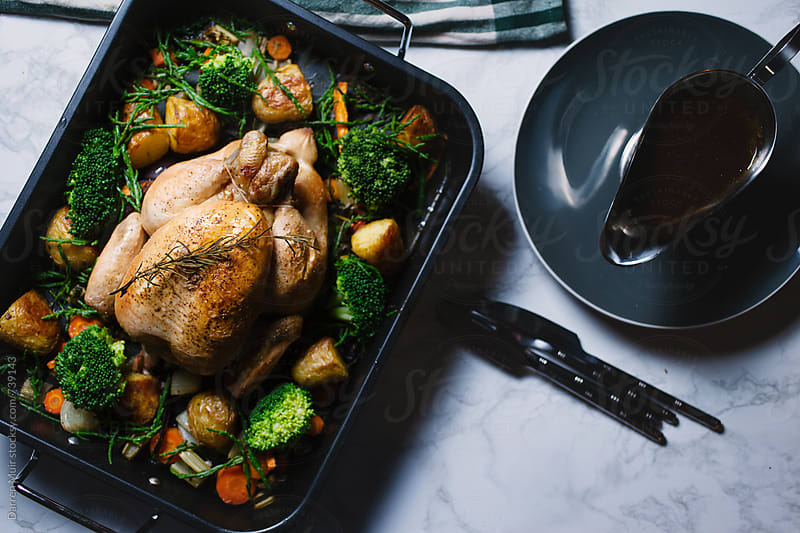 Roast chicken dinner served in a roasting tray with a gravy boat. by Darren Muir for Stocksy United