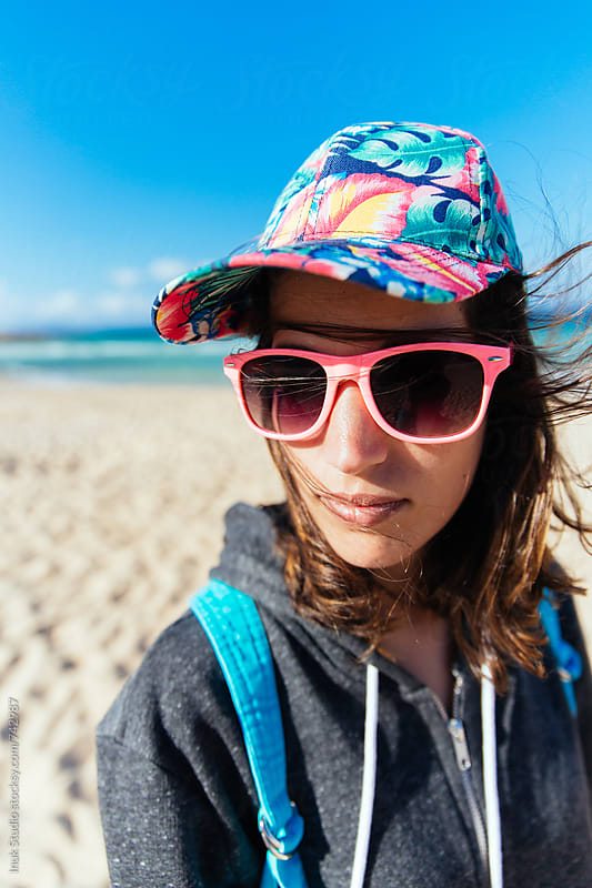 Hipster young woman wearing pink sunglasses and a colourful cap in a beach on a windy day by Inuk Studio for Stocksy United