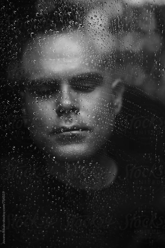 Portrait of a man watching rain through window by Jovana Rikalo for Stocksy United