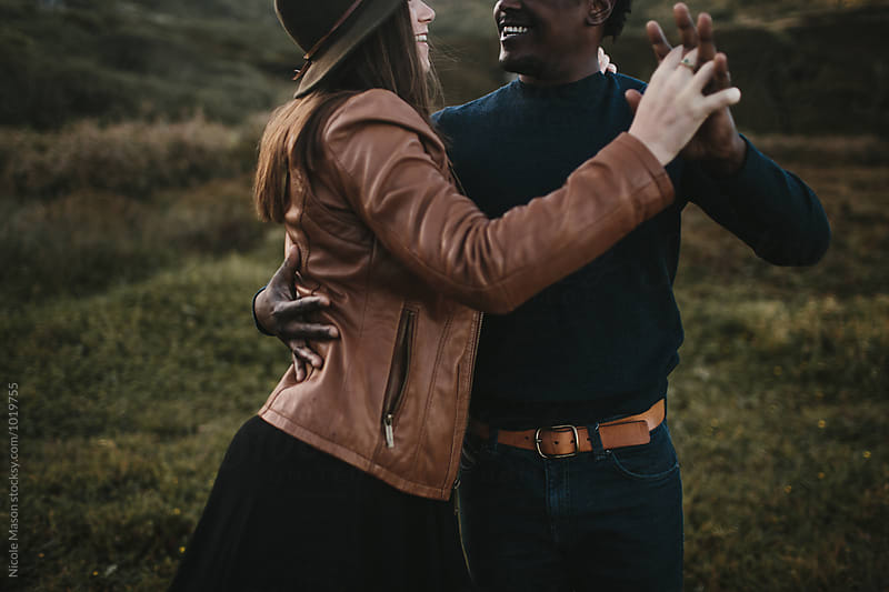 couple hugs holding hands laughing in a field by Nicole Mason for Stocksy United