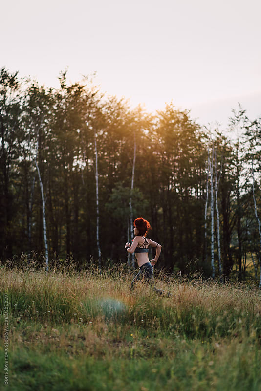 Attractive young woman running through the forest by Boris Jovanovic for Stocksy United