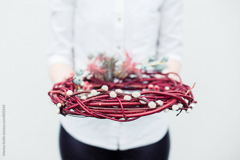 A red wooden wreath being held by an anonymous female in a white shirt by Maresa Smith for Stocksy United